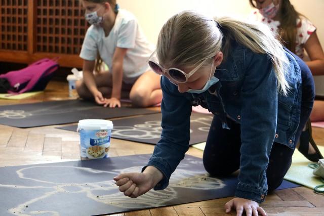 Wakacyjne zajęcia etnograficzne, to świetna okazja, by połączyć te dwa letnie motywy i z drobnego pisaku wyczarować ozdobne dywany. Sięgniemy tu do kujawskiej tradycji wysypywania kwietnych wzorów, które przez dziesięciolecia tworzono w tym bogatym w ludowe tradycje regionie. Razem z etnografem grudziądzkiego Muzeum – Łukaszem Ciemińskim poznaj ten ciekawy zwyczaj.