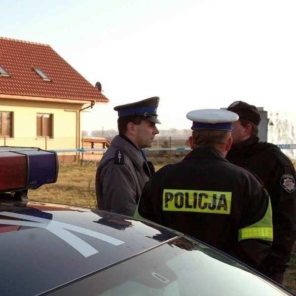 Policjanci przed domem, obok którego znaleziono ciało kobiety i mężczyzny.