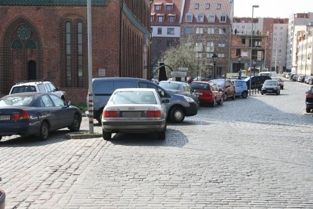 Parkowanie na starówceNa parkingu zabraklo miejsca, to kierowca zostawil samochód obok parkingu blokując ruch.