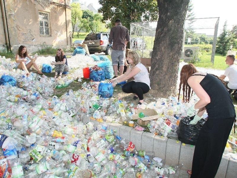 Wolontariusze pomagają czyścić butelki.