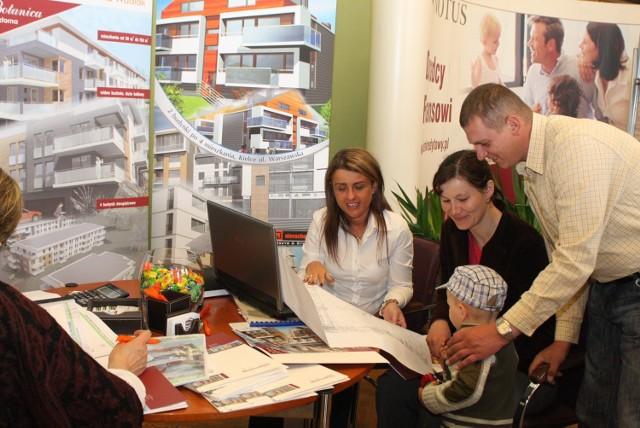 Katarzyna Barańska z firmy Ryszard Grzyb Nieruchomości–Budowa–Kupno–Sprzedaż prezentuje ofertę Annie i Mirosławowi Kwiatek, którzy na targi przyszli z synkiem Karolem.