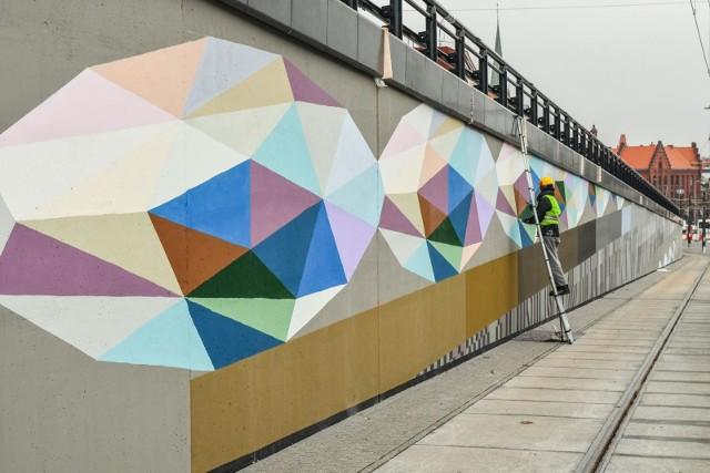 Bydgoskie murale powoli stają się znakiem rozpoznawczym miasta. Nie tylko mają za zadanie promować Bydgoszcz, ale także nadają miastu kolorytu i pokazują, że nad Brdą mieszkają ludzie twórczy.Jeden z najnowszych murali powstaje na murach oporowych budowanej linii tramwajowej na ul. Kujawskiej. Prace są już prawie na finiszu. Malowidło ma być gotowe do końca listopada.