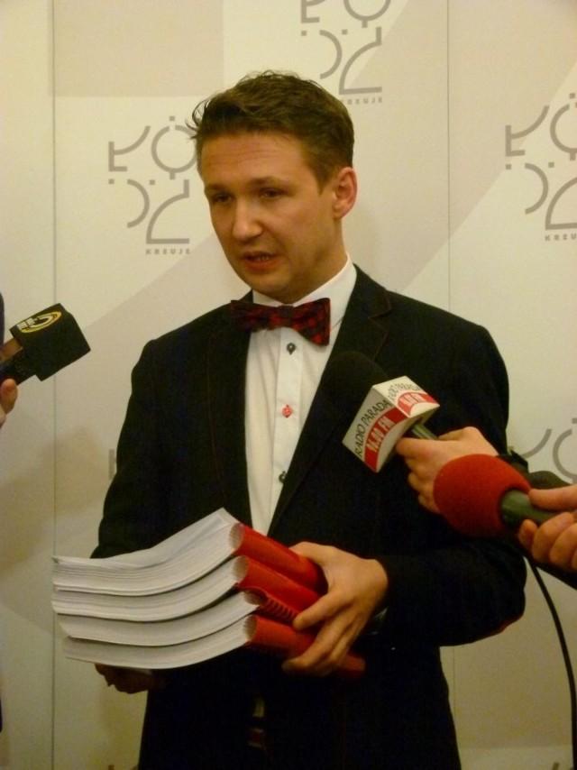 Dyrektor Marcin Górski z czterema tomami dokumentów o umowach urzędu.