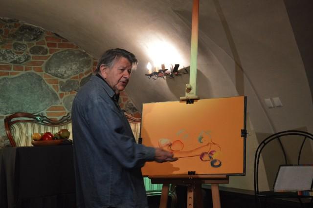 Janusz Trzebiatowski przy sztaludze. Malował i jednocześnie tłumaczył, na czym polega technika pasteli.