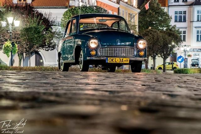Zabytkowe auto na tle zabytków Kluczborka, sfotografowane w nocnej poświacie - tak wygląda oryginalna sesja fotograficzna Łukasza Turka.Niebieska ślicznotka, a w tle Kluczbork nocą - ślicznotka to zabytkowa Syrena 104, rocznik 1970, przebieg 80 tysięcy km, z drzwiami otwieranymi do tyłu, czyli popularnymi kurołapami. Zabytkowy samochód został sfotografowanym w różnych miejscach Kluczborka przez Foto-Luka, czyli Łukasza Turka.- Zdjęcia robiliśmy późnym wieczorem i w nocy nie tylko dla lepszego efektu, ale także dlatego, żeby nie było gapiów na zdjęciach - tłumaczy Łukasz Turek. Mimo późnej pory zabytkowe auto na ulicach Kluczborka i tak wzbudziło sensację, a reakcje nie zawsze były pozytywne. - Kiedy wjechaliśmy na rynek, kilka starszych osób zareagowało oburzeniem, że jeździmy takim gruchotem i kopcimy spalinami - śmieje się Łukasz Turek. - Większość osób była jednak zaintrygowana tym motoryzacyjnym cackiem. Wszyscy oglądają się za tym autem. Taki zabytkowy wóz robi lepsze wrażenie niż nowy mercedes!Łukasz Turek jest twórcą strony Moto-Foto-PRL, na której umieszcza zdjęcia zabytkowych samochodów produkowanych w czasach słusznie minionych.- Warto pokazywać te zabytkowe samochody, ponieważ młodzież już ich nie pamięta. Nastolatki, które podchodziły do nas w czasie sesji fotograficznej, nie miały pojęcia, co to za auto. Zgadywali, że to może wartburg albo trabant! - dodaje Łukasz Turek. Kluczborski fotografik dodaje, że ta oryginalna sesja będzie miała ciąg dalszy. - Może będą inne miejsca, może inny samochód. Szczegółów na razie nie mogę zdradzić - mówi Łukasz Turek. Dodajmy, że Syrena 104 produkowana była w Polsce w latach 1966–1972. Miała silnik o pojemności 842 cm3 i mocy 40 koni mechanicznych. Była ostatnim modelem Syreny z z kurołapami, czyli drzwiami otwieranymi do tyłu.Zobacz na mapie, jaką trasę pokonała podczas sesji fotograficznej kluczborska Syrena 104: