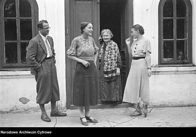Grupa osób przed domem (Choiny, 1935).Na zdjęciu widoczna jest m.in. Danuta Jankowska-Magierska (1. z prawej) w sukience z pasem. Dalej znajduje się starsza kobieta, dziewczyna w spódnicy i swetrze oraz mężczyzna w okularach - niezidentyfikowani.źródło: Archiwum Fotograficzne Stanisława Magierskiego (NAC)
