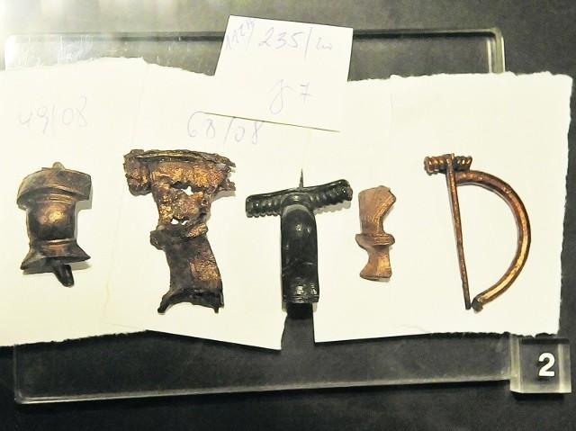 Brązowe zapinki pochodzą z grobów cmentarzyska ludności kultury wielbarskiej (II-III w p.ne.) w Jordanowie na stanowisku 12