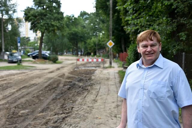 Zbigniew Klimaszewski stoi na terenie dawnej Korony. Drzewa rosnące po lewej stronie ulicy to już dawna Litwa