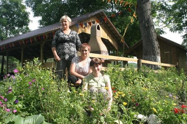 Katarzyna Wojciechowska (na dole), Zuzanna Wojciechowska i Krystyna Niegłos mówią, że Mościczanie potrafią się skrzyknąć i zrobić coś dla wsi. Za nimi wiata i ozdobne kwiaty na placu wiejskim.
