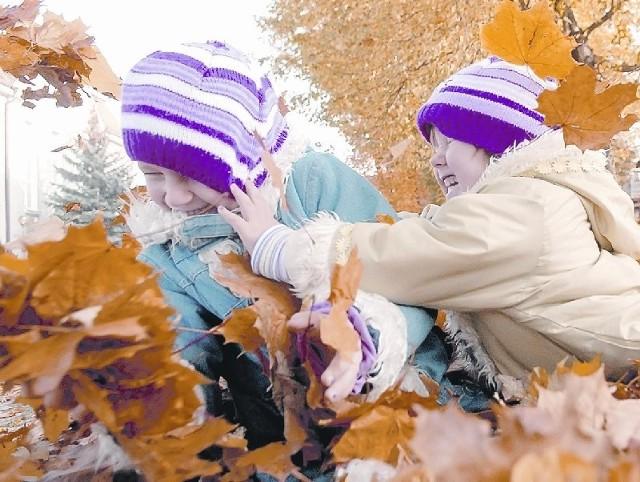 Iga i Zosia Olszewskie szaleją w kolorowych liściach, jakie opadły z drzew na pl. Powstańców Wielkopolskich w Zielonej Górze