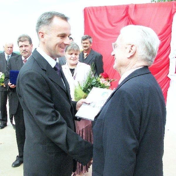 Na zdjęciu Henryk Kulczyk odbiera od  burmistrza Waldemara Stupałkowskiego akt  nadania honorowego obywatelstwa Wałdowa. W  tle rada sołecka.