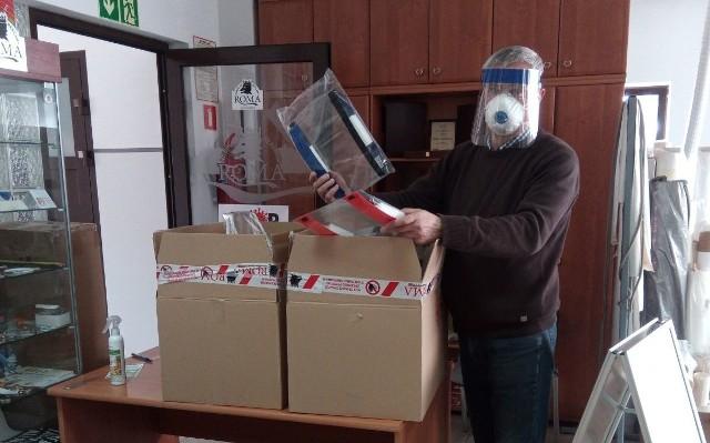 Pan Janusz prezentuje wyprodukowane przez jego firmę przyłbice