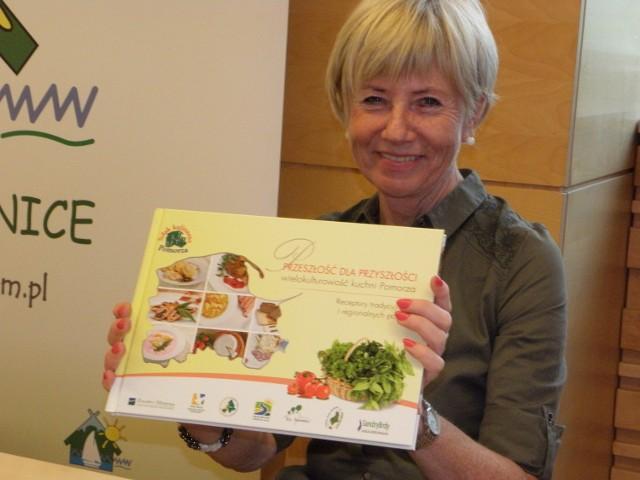 Grażyna Wera-Malatyńska prezentuje książkę wydaną przez lokalne grupy działania z Pomorza