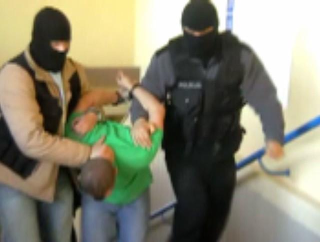 Jeden z zatrzymanych prowadzony przez policjantów.