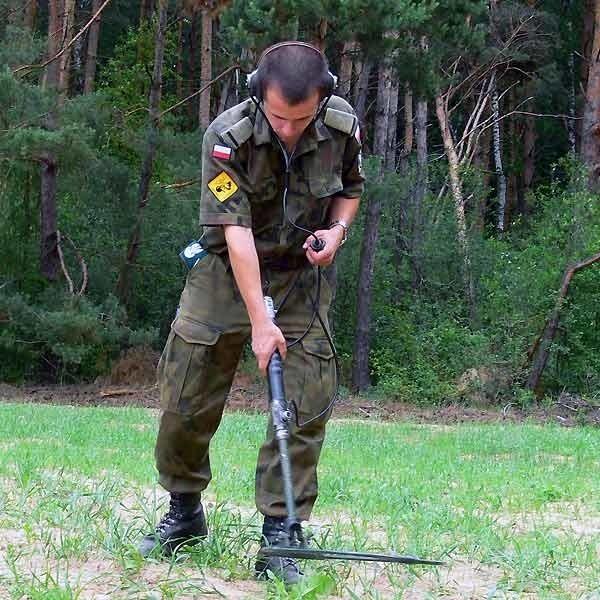 St. szer. nadterminowy Krzysztof Frei sprawdza poszukiwaczem min, czy w pobliżu znalezionego pocisku nie ma innych.