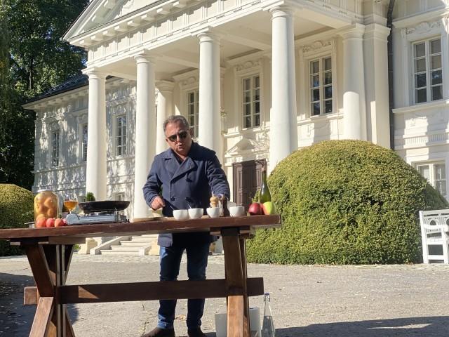 Robert Makłowicz przed Pałacem Mała Wieś w trakcie nagrywania kulinarnych podróży.