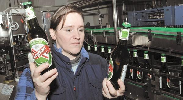 Anna Siekiera, pracownica produkcji połczyńskiego browaru, sprawdza, czy etykiety na butelkach z nową marką piwa są na swoim miejscu. Wcześniej wygląd etykiet zaakceptowali kibice Legii Warszawa.
