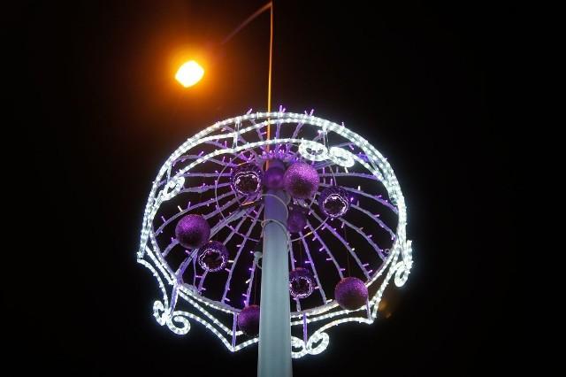Architektura ożywa nocą, a świąteczne dekoracje zaraz po zmroku. Zobaczcie jak jest wieczorem w Nowej Soli.Na rondzie Dozametu w Nowej Soli wiszą bombki. Z samochodu można je zobaczyć w dzień, a kiedy zapada zmrok okrywają je światełka oryginalnych parasoli, które wiszą na latarniach. To zupełnie nowe ozdoby w naszym mieście. Rondo zostało otwarte kilka miesięcy temu, więc i ozdoby są nowe, zakupione przez urząd miasta na właśnie te święta. Świetlne parasolki wyglądają pięknie o każdej porze. My fotografowaliśmy je wieczorem. Jak co roku również nowosolski magistrat zachwyca oświetleniem. A spadające komety na drzewach w centrum miasta przyciągają wzrok przechodniów.Czytaj też: Mamy gotową kolejną fabrykę w Nowej Soli;nfZobacz: Centrum Moskwy rozbłysło feerią barw. Świąteczne iluminacje widziane z lotu ptaka