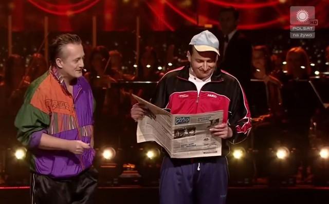 """Mikołaj Cieślak (z lewej) i Robert Górski z Kabaretu Moralnego Niepokoju podczas skeczu, którego akcja działa się w 1997 roku. Na scenie wspominali tamten czas korzystając z wiadomości """"Echa Dnia""""."""