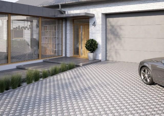 Podjazd do garażu z płyt betonowych i kamykówDo budowy podjazdu do garażu można wykorzystać betonowe płyty ażurowe i wypełnić je kamyczkami.