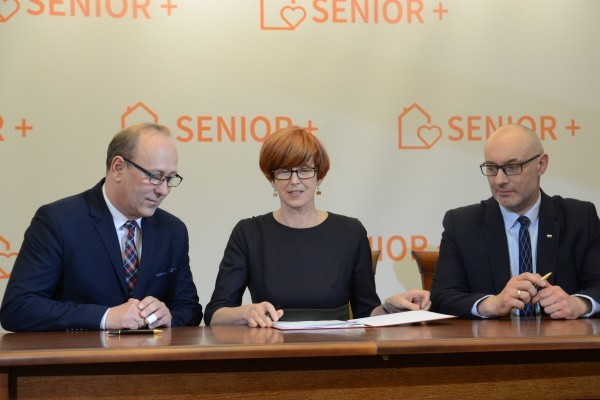 Minister Elzbieta Rafalska i burmistrz Krzysztof Łobos podczas podpisania umowy. Obok wojewoda opolski Adrian Czubak.