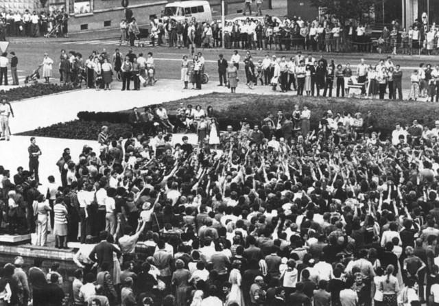 """Ta fotografia została wykonana w trakcie patriotycznej manifestacji, do której doszło 31 sierpnia 1982 roku, w centrum Koszalina. To między innymi o niej piszą esbecy w swoim raporcie. Na zdjęciu widać tłum ludzi, z których część podnosi ręce z palcami w kształcie litery """"V""""."""