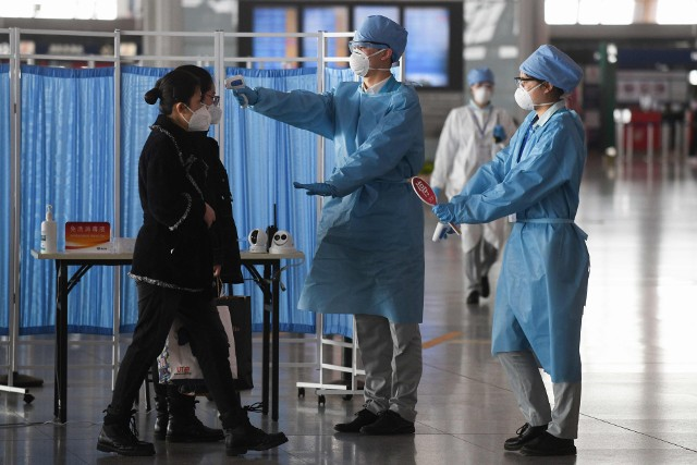 Sprawdzanie temperatury pasażerów na lotnisku w Pekinie