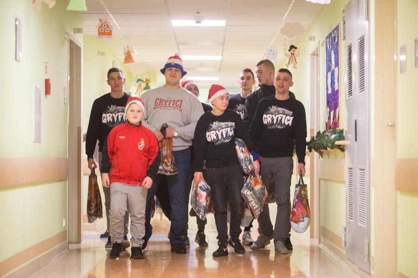 Kibice Gryfa Słupsk zebrali się by przekazać paczki dla dzieci które spędzą święta w słupskim szpitalu. Przynieśli gadżety z logo gryfa, słodycze i owoce. Młodzi pacjenci byli pozytywnie zaskoczeni.