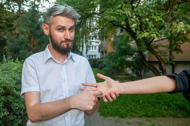 """Jacek Kowalski, tłumacz-przewodnik osób głuchoniewidomych pokazuje literę """"N"""""""