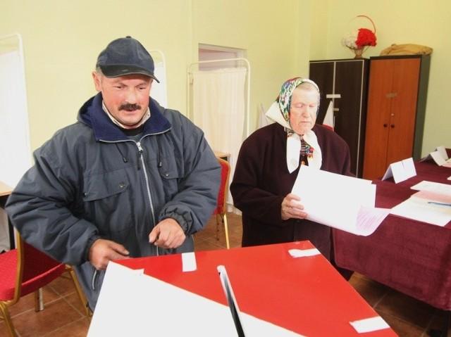 Karty do urny wrzucają pani Maria i pan Andrzej z Podzamcza Piekoszowskiego.