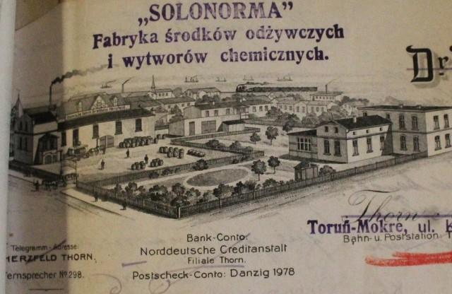 Fabryka Herzfelda i Lissnera na rogu ul. Kościuszki i Batorego w Toruniu. Ilustracja pochodzi z papieru firmowego użytego do korespondencji z magistratem w momencie przejściowym. Częściowo przekreślony nadruk oryginalny jest jeszcze w języku niemieckim, pieczątka nad obrazkiem jest już jednak polska - z nową nazwą fabryki.Ilustracja, chociaż na pierwszy rzut oka może się wydawać fantazją, raczej wiernie odwzorowywała rzeczywistość. Z lewej strony widzimy charakterystyczny budynek, który stał przy ul. Batorego, zza niego wystaje natomiast dach istniejącej do dziś kamienicy Antoniego Kamulli, który jak wiadomo był piekarzem, a poza tym posiadaczem pierwszego prawa jazdy w Toruniu.