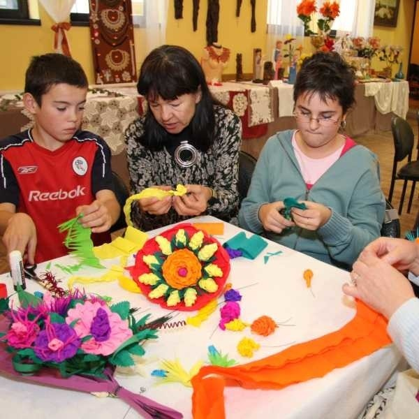 Uczestnicy warsztatów artystycznych  w trakcie tworzenie kwiatów z papieru. Od lewej: Patryk Kościelny, Izabella Terlecka, Joanna Kucińska.