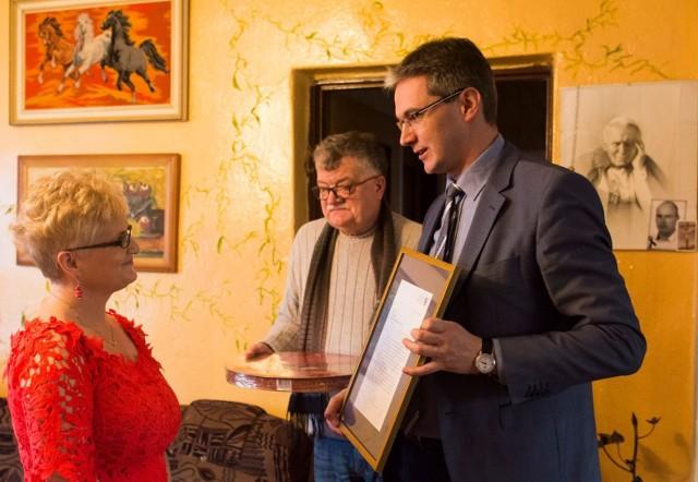 Marszałek województwa Adam Jarubas ze swoim doradcą Adamem Ochwanowskim wręczają Ewie Naporze list gratulacyjny i nagrodę jubileuszową.