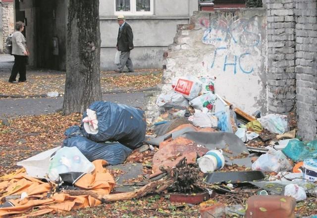 Sterty śmieci na podwórku przed budynkiem - tuż obok jest z nich usypana góra prawie na wysokość pierwszego piętra