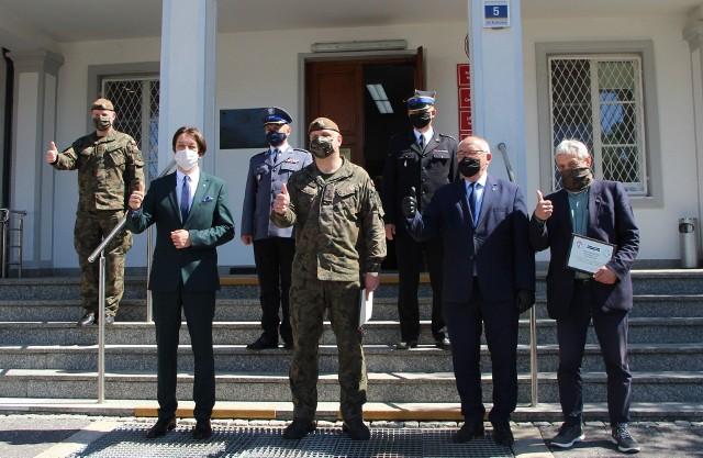 Podpułkownik Łukasz Baranowski (w środku) w towarzystwie kozienickich samorządowców i przedstawicieli policji i straży pożarnej.