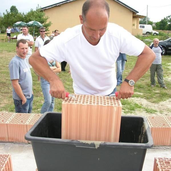 Robert Iwanicki próbuje przekonać do klejenia cegły szlifowanej, demonstrując materiał na budowie własnego domu.