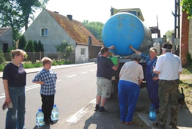 - Beczkowozem mogę stanąć tylko tam, gdzie nie ma niebezpieczeństwa dla ruchu drogowego. Niech ludzie wystawią przed dom bańki na wodę, lub wywieszą szmatkę, wtedy będę wiedział, kto potrzebuje wody - mówi Stefan Trojnacki (drugi z prawej), który wczoraj rozwoził wodę dla mieszkańców.