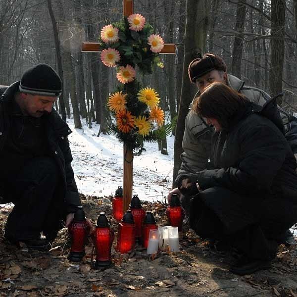 Beata Szady, żona zabitego mężczyzny i jego brat Janusz (z lewej), palą znicze na miejscu tragedii.