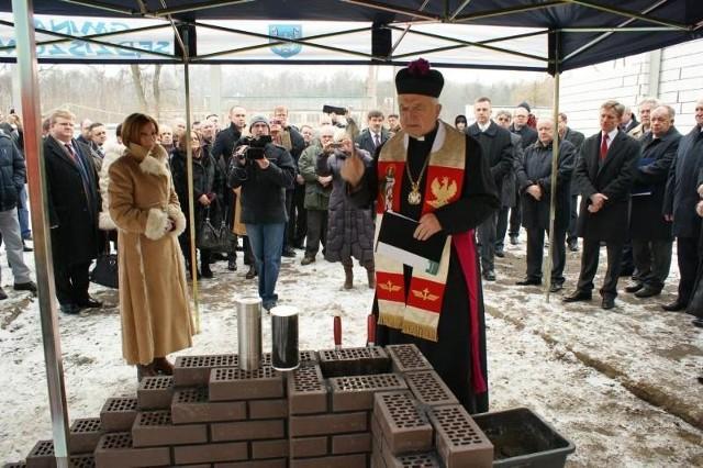 Ksiądz Marian Haczyk dokonuje poświecenia kamienia węgielnego przed wmurowaniem. Obok Marzena Gładka, prezes firmy Fluid S.A.