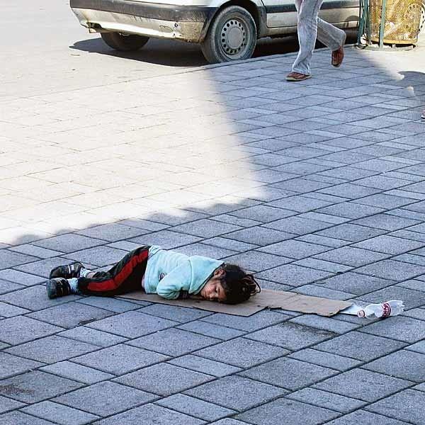 Centrum Tirany. Na kawałku tektury śpi małe dziecko. Przechodnie rzucają mu jałmużnę.