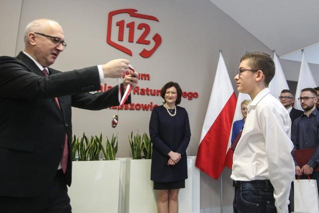 """Dziś minister Joachim Brudziński otworzył nowy budynek Centrum Powiadamiania Ratunkowego w Rzeszowie. To pierwszy w Polsce obiekt wybudowany od zera z przeznaczeniem na centrum powiadamiania. Na razie znajduje się w nim 19 stanowisk operatorskich, ale obiekt pozwala na zwiększenie ich liczby do 40. Całość kosztowała ponad 8 mln zł, a pieniądze pochodziły z rezerwy celowej budżetu państwa.Podczas wizyty na Podkarpaciu szef MSWiA wręczył też wyróżnienia dla 10 operatorów numeru 112. Medalem i tytułem """"Młody bohater"""" Brudziński nagrodził też 12-letniego Bartka Purchę z Jarosławia, który we wrześniu 2017 r. wybrał numer 112 i wezwał pomoc do słabnącej na przystanku autobusowym starszej kobiety. ZOBACZ TEŻ: Sala do badań biologicznych w 2 Klinice Pediatrii w Rzeszowie"""