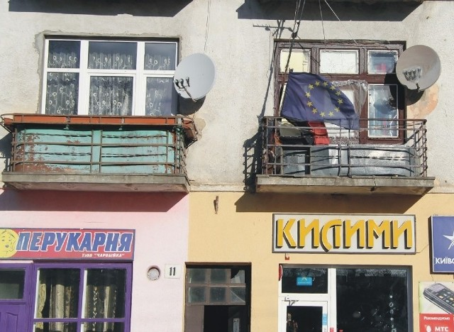 Skrajności na Ukrainie. Na balkonie kamienicy w przygranicznych Mościskach wiszą flagi unijna i nacjonalistyczna-ukraińska.