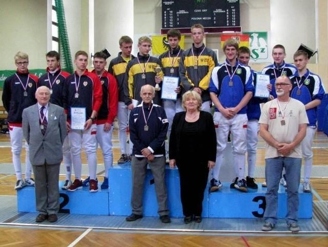 Przed podium trener Adam Medyński ze swoją złotą ekipą oraz Olga Walewska, prezes Dolnośląskiego Związku Szermierczego.