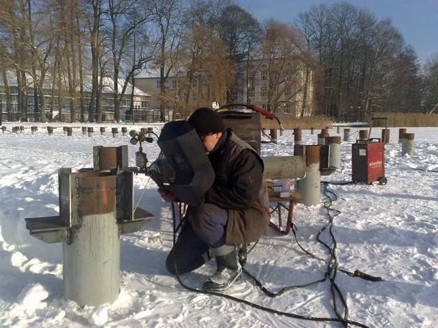 Robotnicy spawają stalowe podpory do pali pomostu na Trzesiecku korzystając z zamarzniętego jeziora.