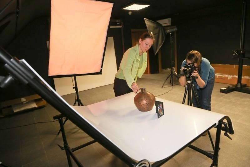 Monika Więcław, pracownica Muzeum Podlaskiego stawia na stole bezcieniowym dawne naczynie, a Anna Sierko-Szymańska fotografuje eksponat. Zdjęcie znajdzie się na stronie internetowej.