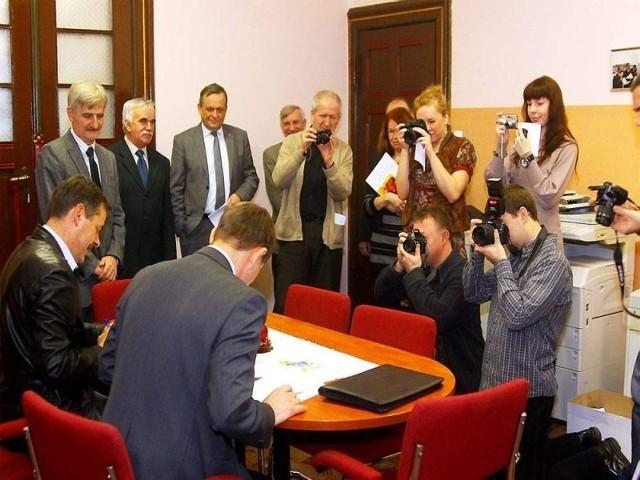 podpisują porozumienie w sprawie MZK, flesze błyskają