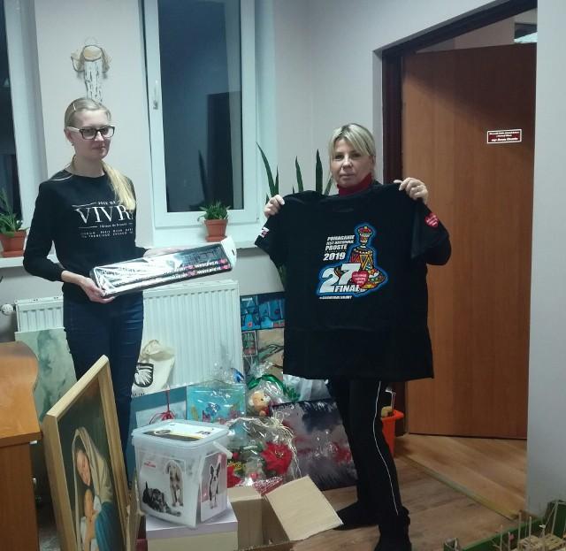 Gadżety przeznaczone na aukcję WOŚP w Wąbrzeskim Domu Kultury prezentują Dorota Otremba (z prawej) i Karina Krzemińska