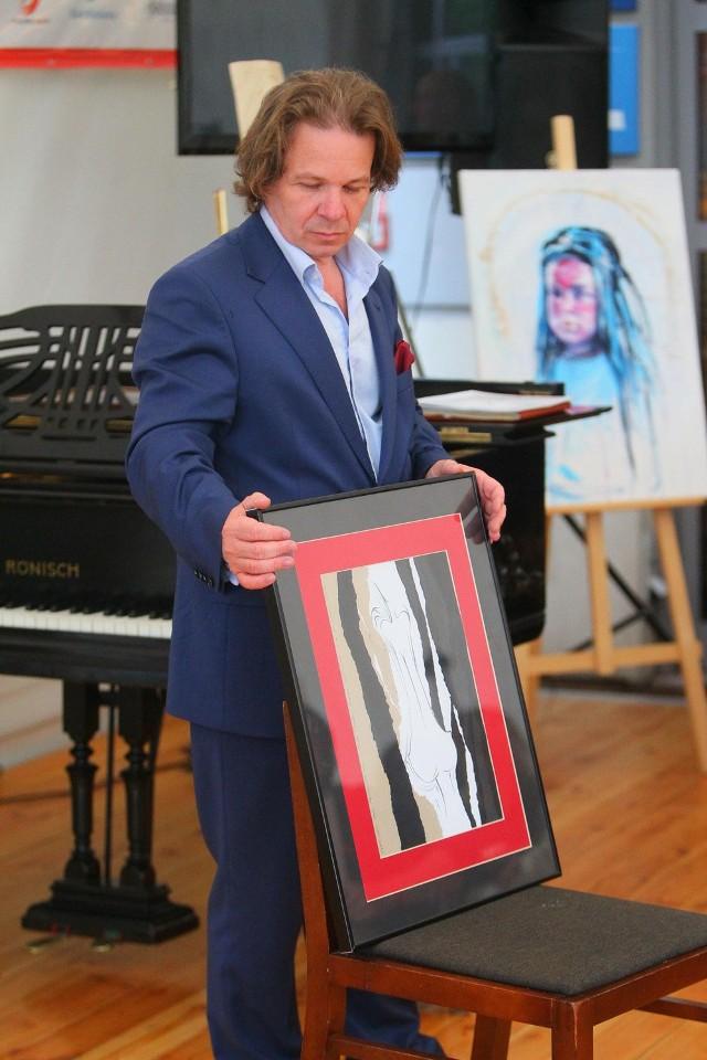 Inicjator Tennis Art Cup Waldemar Górka prezentuje jedną z prac podczas aukcji.