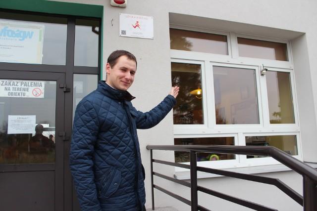 Ks. Paweł Filipiak pokazuje sensor zamontowany na budynku Szkoły Podstawowej nr 6 w Chrzanowie
