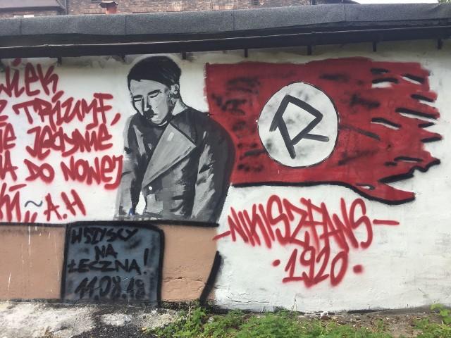 """Na ścianie jednego z garaży na Nikiszowcu w Katowicach pojawił się skandaliczny mural z wizerunkiem Adolfa Hitlera i cytatem z Mein Kampf. Z kolei w koło na fladze zamiast swastyki wpisana jest literka """"R"""" symbol Ruchu Chorzów. Sprawą zajmuje się już Prokuratura Rejonowa Północ w Katowicach, a policjanci badają sprawę. Mural został też zamalowany."""